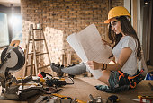 Female construction worker analyzing housing project during renovation process.