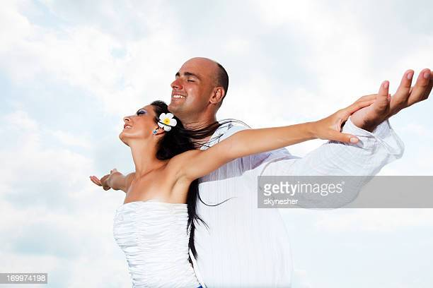 Beautiful married couple against the sky.