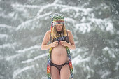 Young mom to be, pregnant and posing in snowy landscape
