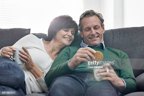 Beautiful mature couple relaxing on sofa with cup of coffee