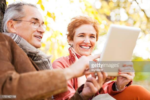 Beautiful mature couple using digital tablet.