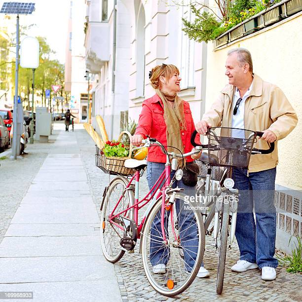 Beautiful mature couple with cycles in the city