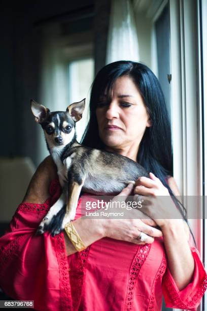 A beautiful mature woman holding a dog and looking throw a window