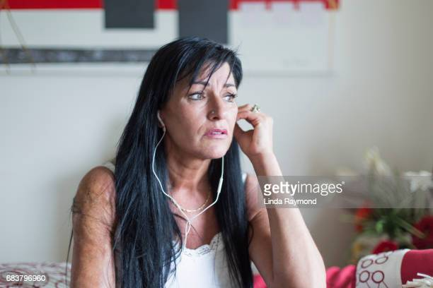 A beautiful mature woman listening to a podcast