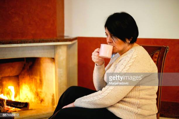 Beautiful mature woman sitting on chair near fireplace and drinking coffe