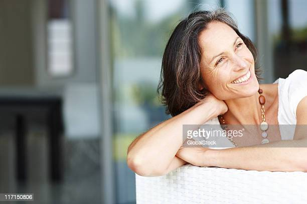 Beautiful mature woman sitting on couch smiling and looking away