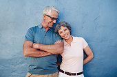 Portrait of beautiful mature woman standing with her husband against blue background. Loving mature couple standing together against a blue wall.
