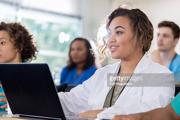 Beautiful medical student uses laptop during class