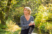 Blonde, short hair, blue eyed, beautiful mid 30's woman thoughtfully looking off while holding a white cup for coffee or tea. The fashionable woman is in an outdoor setting and wearing a pearl necklac