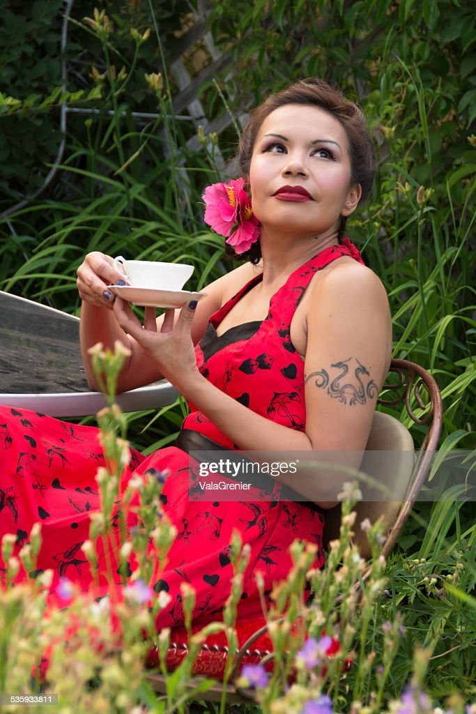 Beautiful mid adult Native woman relaxing with tea in garden. : Stock Photo