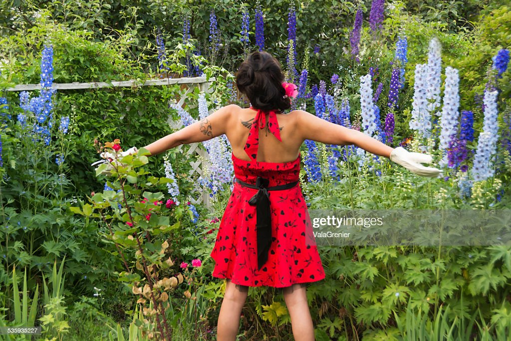 Beautiful mid adult Native woman standing in garden, arms wide. : Stock Photo
