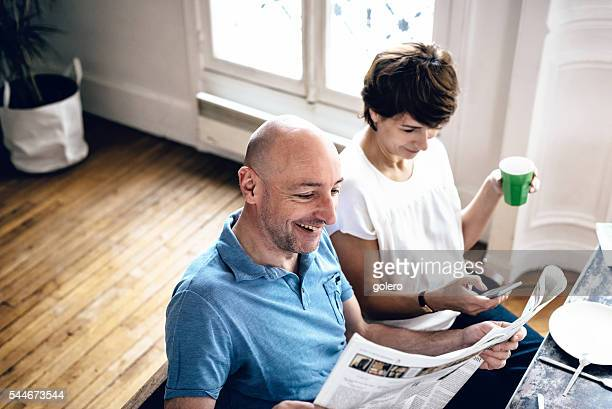 beautiful midaged couple reading news in newspaper and on mobile
