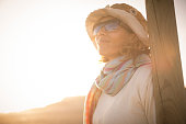 summer time for beautiful 40 years old nice woman looking at the sky with sun backlight. sunglasses and hat bright image.