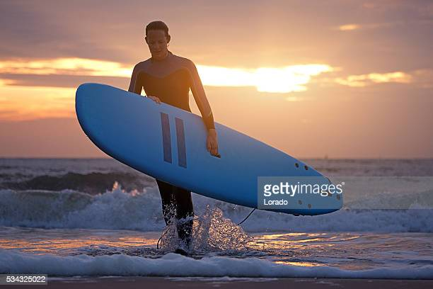 Beautiful middle aged female surfer on beach at dusk