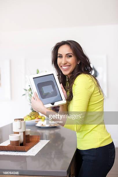 Linda mulher do Oriente Médio usando Tablet em casa a sorrir