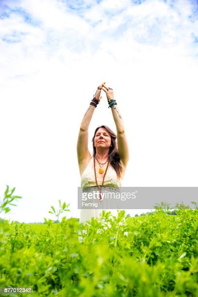 Beautiful, middle-aged woman practising yoga outside in nature