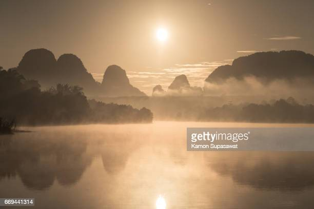 Beautiful mist and reflection of mountain with golden sunrise light into lake 'Nongtalae' in Krabi province in Thailand