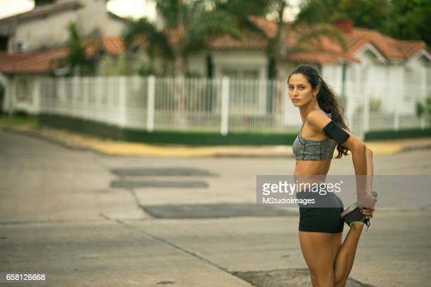 Beautiful mixed race woman stretching at the city