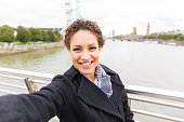 Beautiful mixed race woman taking a selfie in London with Thames river and Big Ben on background. She is holding the camera with one hand and looking at it smiling.