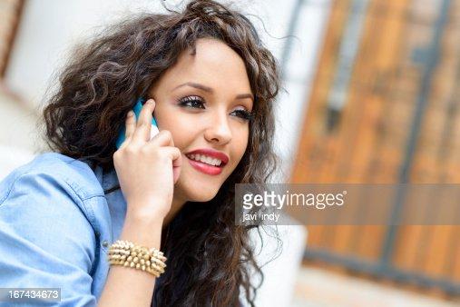 Mixto hermosa mujer en fondo urbano en el teléfono : Foto de stock