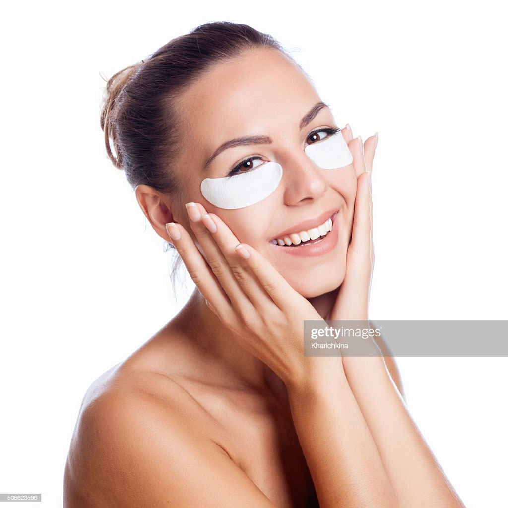 beautiful model applying  cream treatment on her face on white : Stock Photo