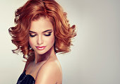 Beautiful model brunette with middle length curled hair and bright make up. Glamour evening style.