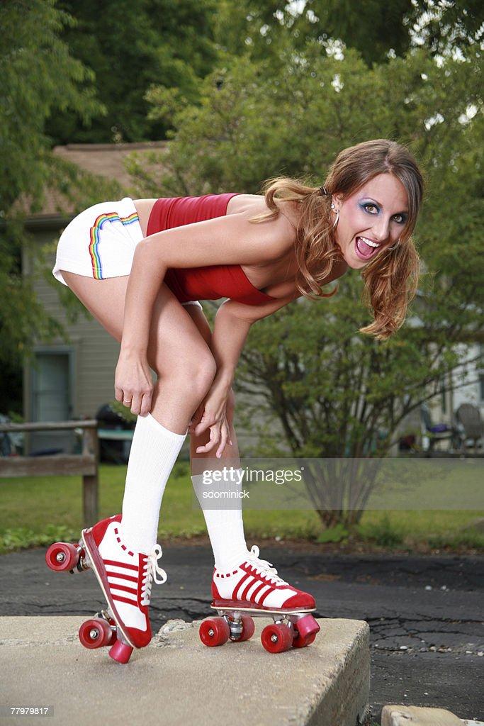 A beautiful model in roller skates pulling up her tube socks.