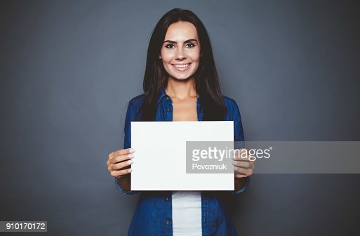 Beautiful modern smiling woman in a jeans shirt with blank sheet of paper for advertising in hands on a gray background isolated. : Foto de stock