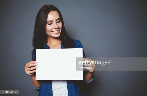 Belle femme souriante moderne dans une chemise en jeans avec feuille blanche pour la publicité en mains sur un fond gris isolé. : Photo
