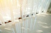 Beautiful morning light through sheer curtain in bedroom