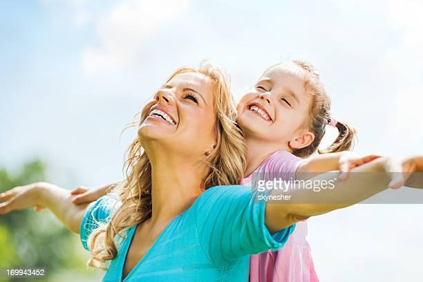 Schöne Mutter und Tochter gegen Himmel.