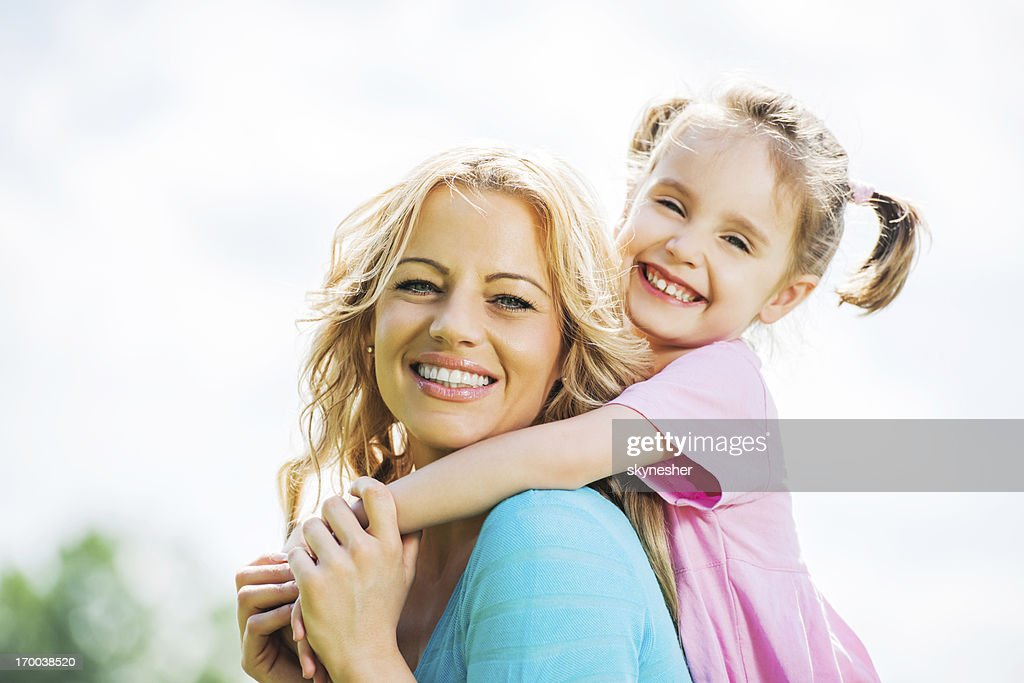 Beautiful mother and daughter against the sky : Stock Photo
