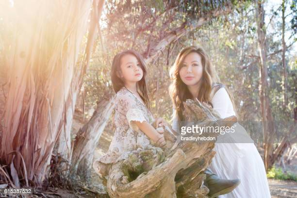 Beautiful mother and daughter relaxing together in forest