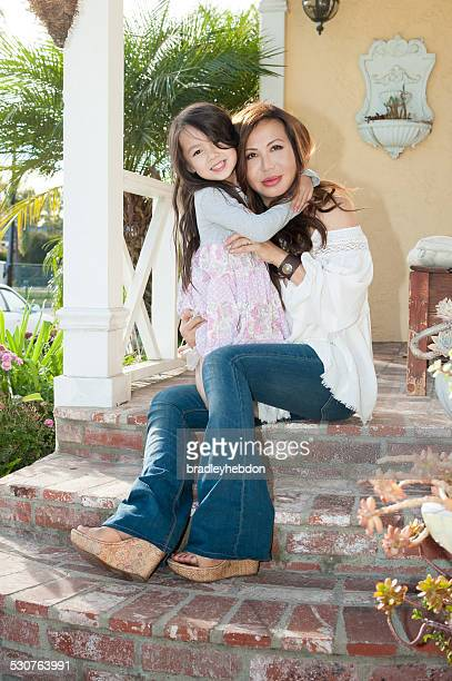 Beautiful mother and daughter sitting on front porch