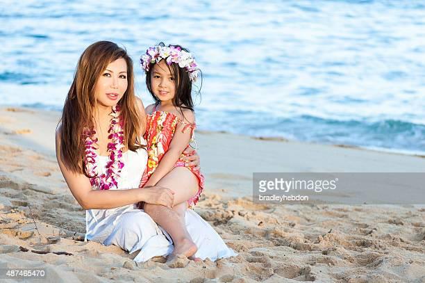 Beautiful mother and daughter wearing Lei on Hawaiian beach