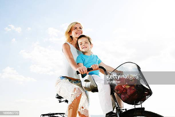 Beautiful mother and her son riding a bike.