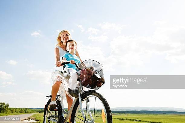Beautiful mother and her son riding a bike