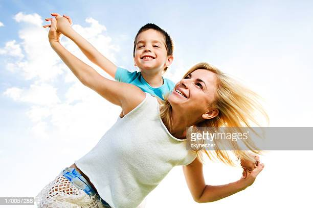 Beautiful mother giving her son a piggyback ride.