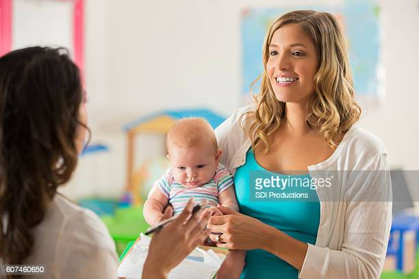 Beautiful mother holding sweet baby and interviewing a daycare teacher