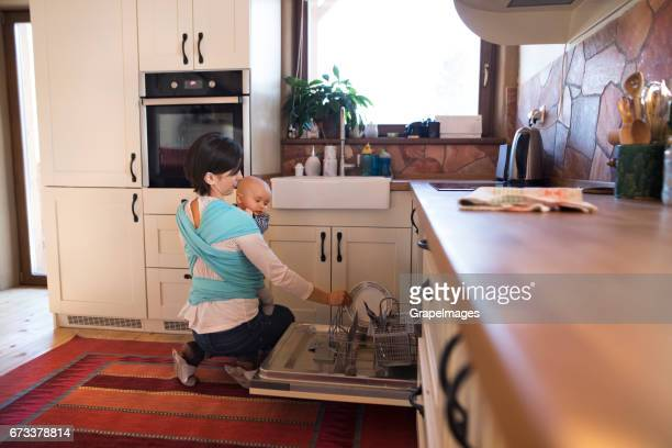 Beautiful mother in kitchen washing dishes, her son in sling