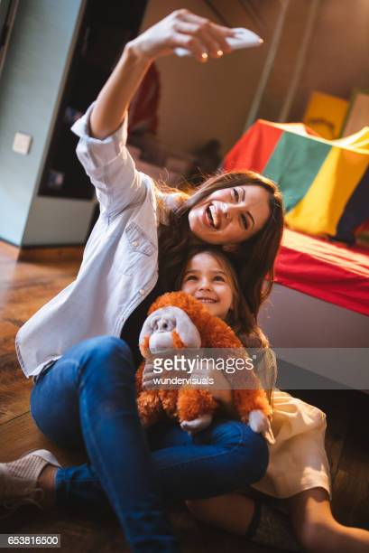 Beautiful mother taking smiling selfie with daughter and her toy