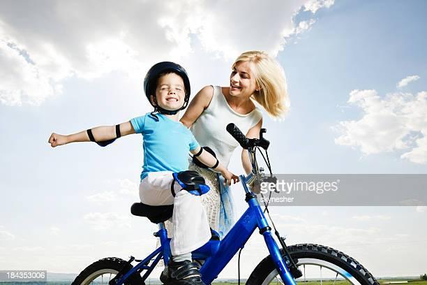 Hermosa madre enseñanza su hijo andar en bicicleta.