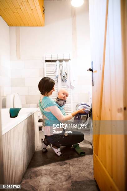 Beautiful mother with baby in sling in bathroom washing clothes