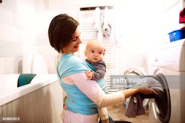 Belle mère avec le bébé dans l'écharpe à laver les vêtements de bain