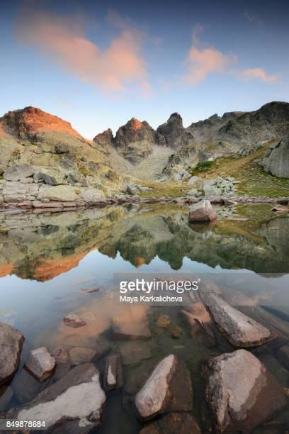 Beautiful mountain lake reflecting peaks at sunset