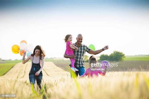 Magnifique multi ethnique famille courir à travers champ de blé