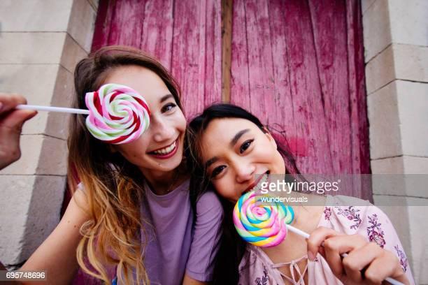 Prachtige multi-etnische tienermeisjes plezier met kleurrijke lollies
