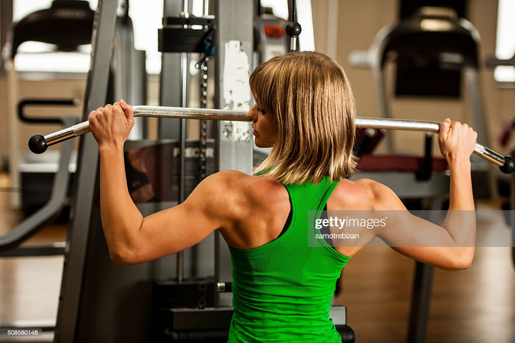 beautiful muscular fit woman exercising building muscles in fitn : Stockfoto