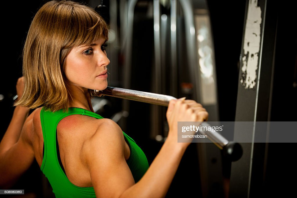 beautiful muscular fit woman exercising building muscles in fitn : Stock Photo