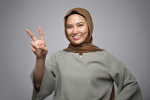 Beautiful Muslim girl gesturing peace sign with smiling face isolate on grey background
